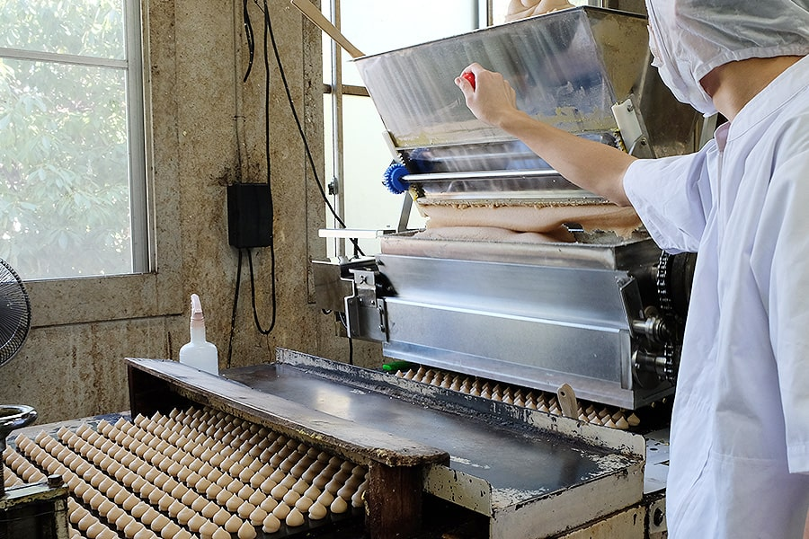 餡を右上の機械にいれて成形していくと……おー!ポテッとした可愛い生の栗しぐれがたくさんできていきます♪